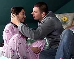 A young girl in pink pajamas is sitting on a bed. A guy next to her is kissing her. The girl lays down and they continue to kiss. The guy then pulls her shirt up in order to lick and kiss her tits before he takes her pants off to lick her pussy.