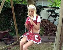 A skinny blonde girl is sitting on a swing, holding a dildo in one hand. She plays with the dildo and looks around to see if no one is watching. She opens her blouse and holds the dildo against her tits, stroking them gently at the same time.